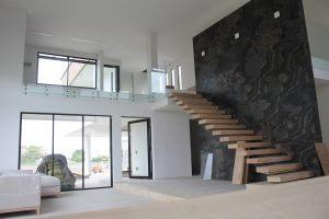 Escaleras en concreto y metal suspendidas, con acabado en madera